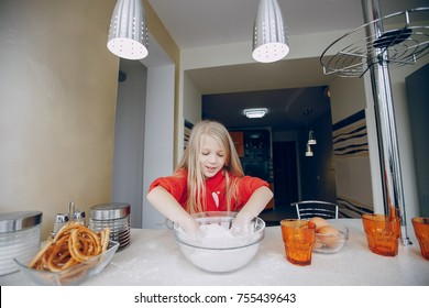 Little beautiful girl at home in the kitchen preparing food and baking cookies
