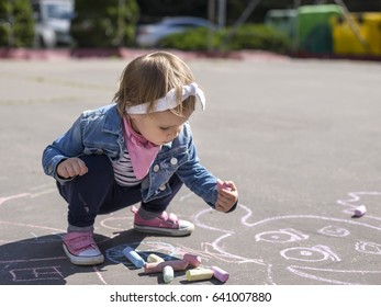 Little beautiful girl in a jeans jacket draws with colored chalks on the playground