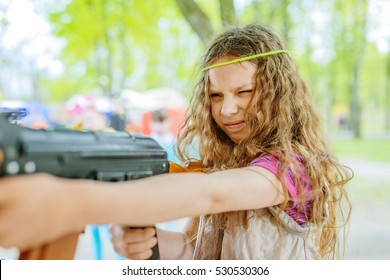 Little beautiful girl with Kalashnikov assault rifle at shooting range in city park in summer.