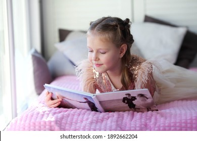 A little beautiful girl lies on the bed and looks at her parent is wedding photo album. Photo printing.