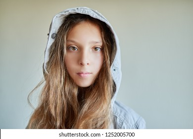 Little beautiful girl with long hair in gray jacket and hood.