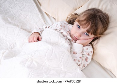 Little beautiful girl lying in bed and holding her cheek with a sick tooth