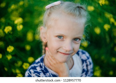 Little beautiful girl on a background of yellow flowers on a blurred background