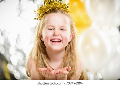 Little beautiful girl at a party New Year with balloons.