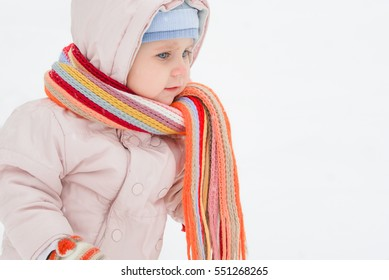 Little beautiful girl in pink overalls and bright multi-colored scarf playing with the snowflakes and smiling during a walk in the snow in the winter
