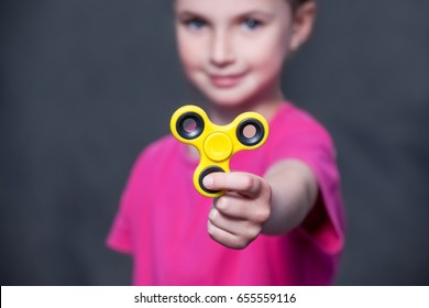 Little beautiful girl in pink t-shirt is playing yellow spinner in hand on the street.