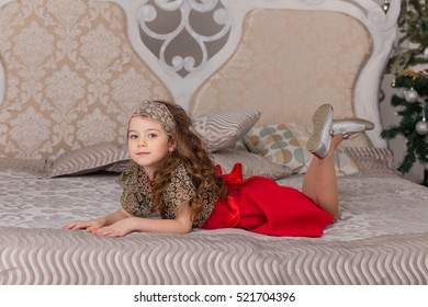 Little beautiful girl in a red evening dress the Christmas tree. Girl in red in Christmas decorations. Cute child on the bed