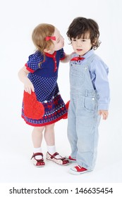 Little beautiful girl with red heart prepares to kiss boy at white background.