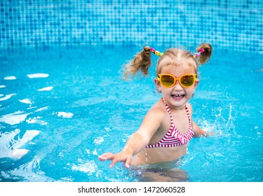 Little beautiful girl resting in the pool and learning to swim