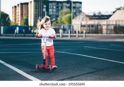 Little beautiful girl riding a scooter
