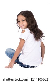 Little beautiful girl sit on the floor in rear pose looks back smile to the camera, isolated on a white background.