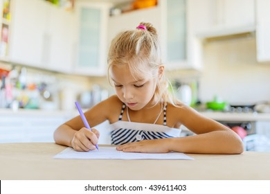 Little beautiful girl sitting at the kitchen table and writing with a ballpoint pen in a notebook.
