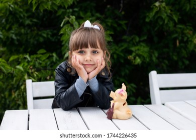 A little beautiful girl is sitting next to the piggy bank and dreaming of what she will spend money on.