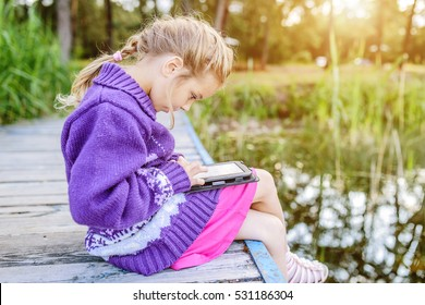Little beautiful girl sitting on a river pier, and read e-books.