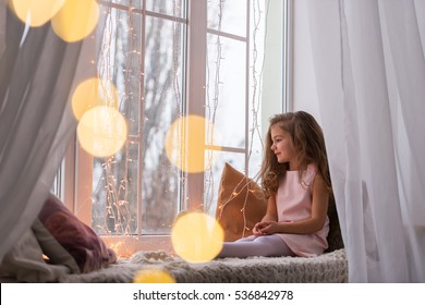 Little beautiful girl sitting on the windowsill, looking at the snow. New Year. Christmas.