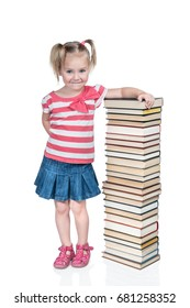 Little beautiful girl smiles slyly leaning on a high stack of books isolated on white background