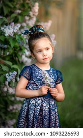 little beautiful girl stands on a lilac background