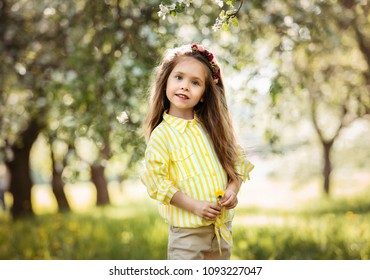 little beautiful girl stands on park background