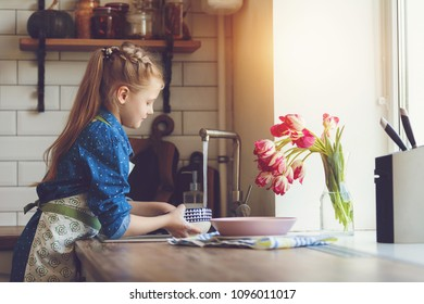 little beautiful girl washes dishes at home in the kitchen