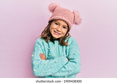 Little beautiful girl wearing wool sweater and cute winter hat happy face smiling with crossed arms looking at the camera. positive person.