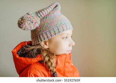 Little beautiful girl in winter hat on light background.