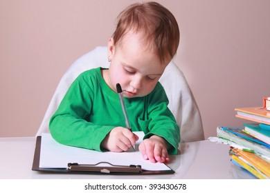 Little beautiful girl writing in her book