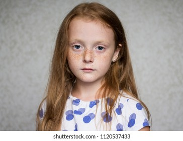 Little beautiful red-haired girl with freckles looking seriously at camera
