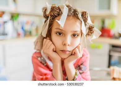 Little beautiful sad girl with hair curlers on her head and pink bathrobe on background of kitchen.