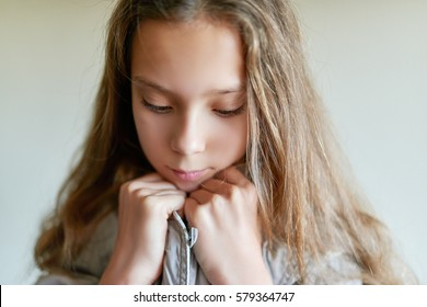 Little beautiful sad girl with long hair in gray jacket.