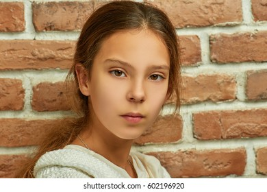 Little beautiful sad girl on background of a brick wall close-up.