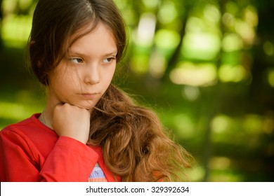 Little beautiful sad girl in red clothes thought, against green summer park.