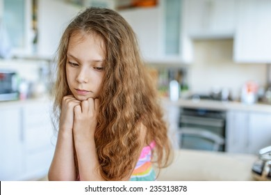 Little beautiful sad girl sitting at kitchen table and think.