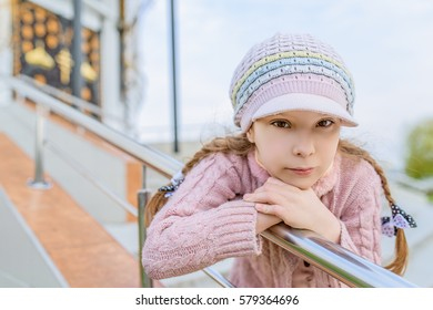 Little beautiful smiling girl in cap near handrail