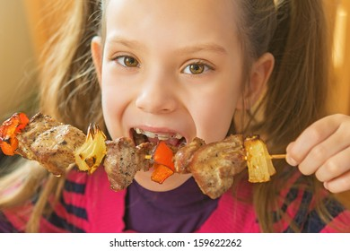 Little beautiful smiling girl eating kebab restaurant.