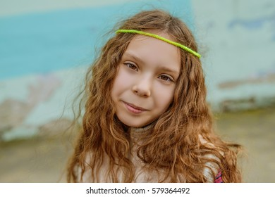 Little beautiful smiling girl with long hair on background of shabby walls.