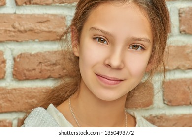 Little beautiful smiling girl on background of a brick wall close-up.