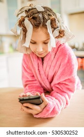 Little beautiful smiling girl with phone and hair curlers on her head and pink bathrobe on background of kitchen.