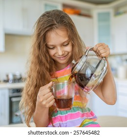 Little beautiful smiling girl pours tea from teapot into cup at kitchen table.