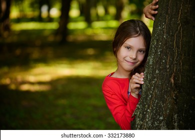 Little beautiful smiling girl in a red dress is hiding behind a tree in the park.