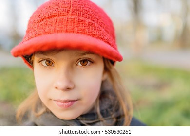 Little beautiful smiling girl in red hat on green background.