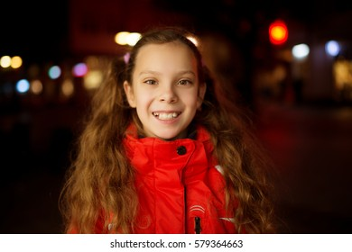 Little beautiful smiling girl in red warm jacket against evening city.