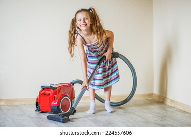 Little beautiful smiling girl running with vacuum cleaner at home.