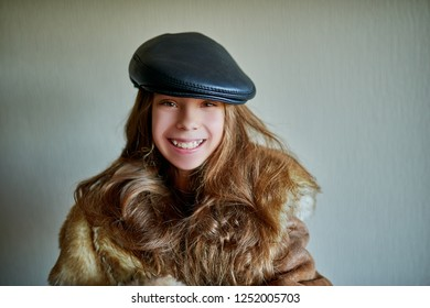 Little beautiful smiling girl in warm fur coat and black leather cap close up.