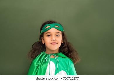 little beautiful superhero girl next to green chalkboard
