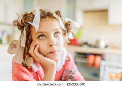 Little beautiful thoughtful girl with hair curlers on her head and pink bathrobe on background of kitchen.