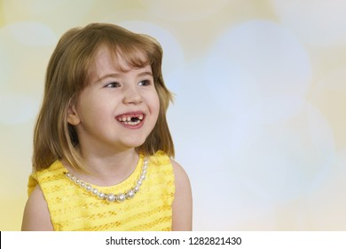 The little beautiful toothless girl laughs merrily. Bright yellow dress and a sun background