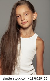 Little beauty concept. Portrait of young girl with long healthy hair wearing summer casual sleeveless t-shirt, posing over gray background. Close up. Studio shot