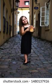 A little beauty girl eats traditional czechian food as named Trdelnik on the streets.