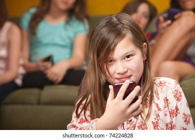 Little Biracial Caucasian and Asian girl listens to a music player