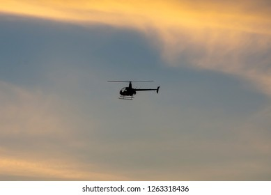 Little bird helicopter flies through sky at sunset. Helicopter tour sightseeing.